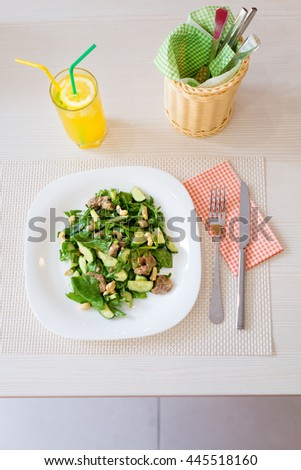 Green tuna salad with nuts and glass of lemon cold drink in restaurant.