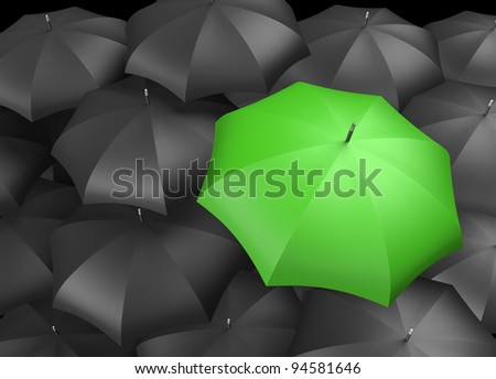 Green umbrella standing out from background of black umbrellas