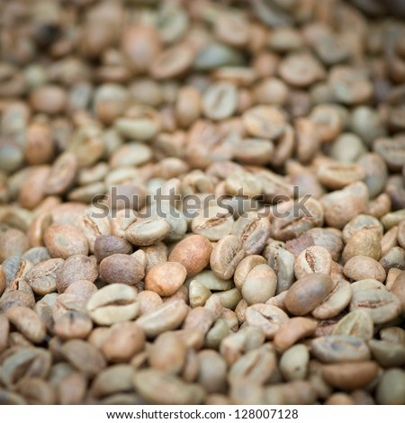 Green un-roasted coffee beans heap with shallow depth of field - stock photo