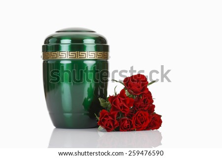 Green urn and red roses on white background - stock photo