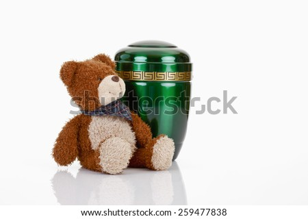 Green urn and teddy-bear - stock photo