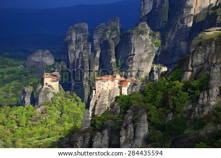 Green valley and Greek monasteries surrounded by dark cliffs, Meteora, Greece - stock photo