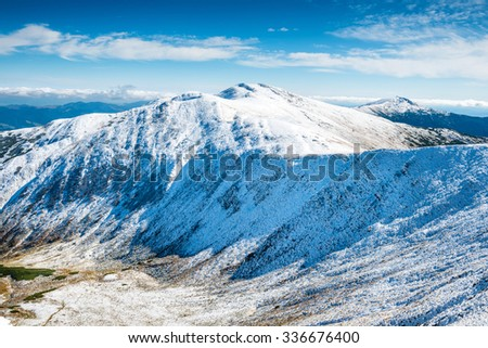Green valley and white peaks of mountains in snow. Winter landscape - stock photo