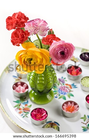 Green vase with flowers - stock photo