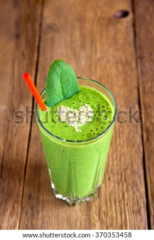 Green vegetable and herbs smoothie with heart of sesame seeds. Love healthy raw food concept. - stock photo