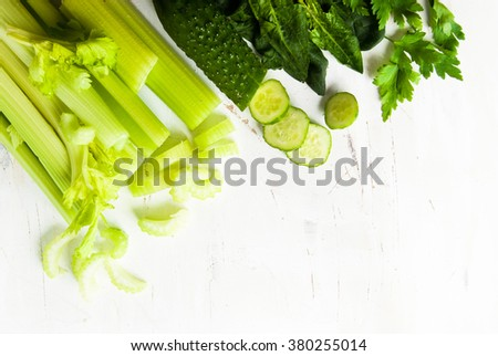 Green vegetable background with celery, cucumber, spinach and herbs on white. Space for text. Healthy food concept. - stock photo