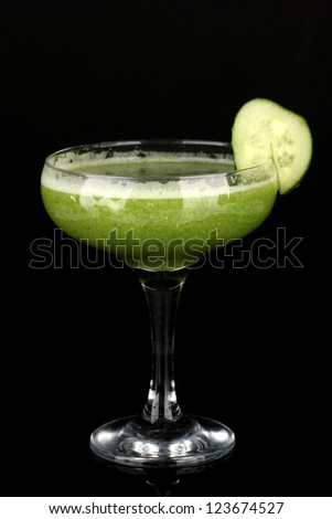 Green vegetable juice in coctail glass isolated on black