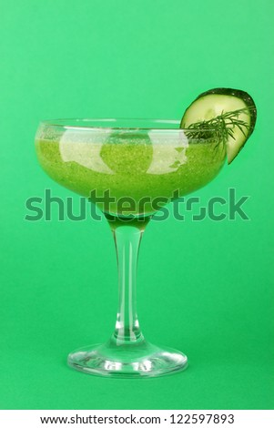Green vegetable juice in coctail glass on green background