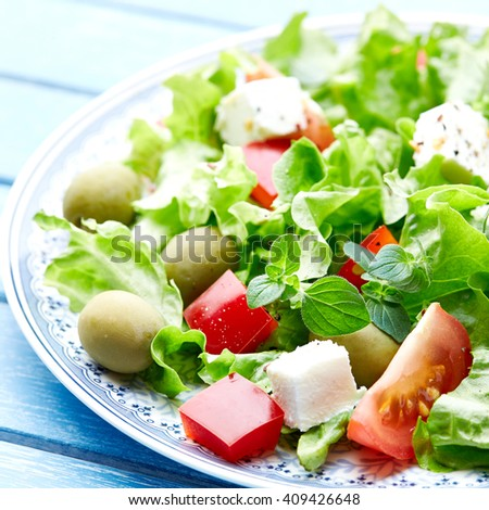 Green Vegetable Salad with Lettuce, Tomatoes, Pepper, Olives and Feta - stock photo