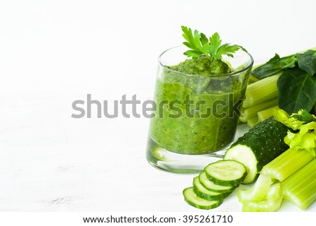 Green vegetable smoothie with celery, spinach and herbs in a asymmetrical glass on a white. Space for text. Healthy food concept. - stock photo