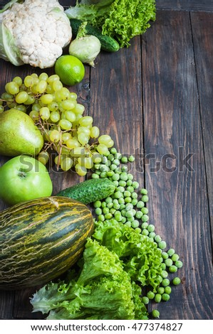green vegetables and fruits on dark wooden background.