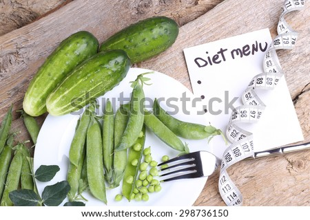 Green vegetables on the table. Pods of green peas, peas and cucumbers. Diet food. Dietary menu. Weight loss, weight gain. Nutritionist. Banner list, note. White measuring tape and fork. Dieting. - stock photo