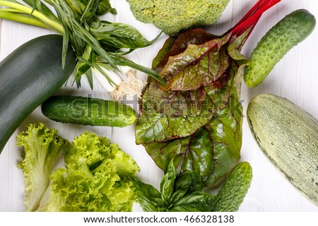 Green vegetables on white wooden background - broccoli, zucchini, lettuce, estragon, green onions, chard, basil, cucumber Top view Flat lay