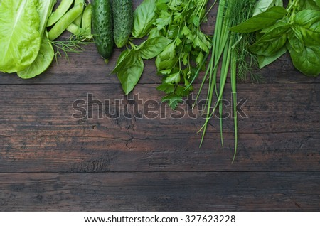 Green vegetables on wooden background (peas, parsley, basil, cucumber, dill, onion ,salad) - stock photo
