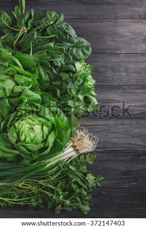 Green vegetables on wooden background (spring onions, parsley, lettuce and spinach)