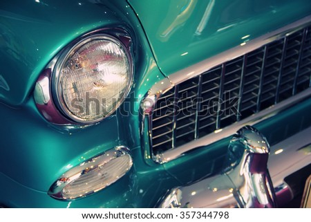 Green vintage car headlight, bumper and grill - stock photo