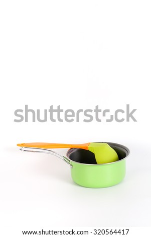 Green Vintage Pot with Colorful dipper,deep spoon isolated on white background and copyspace