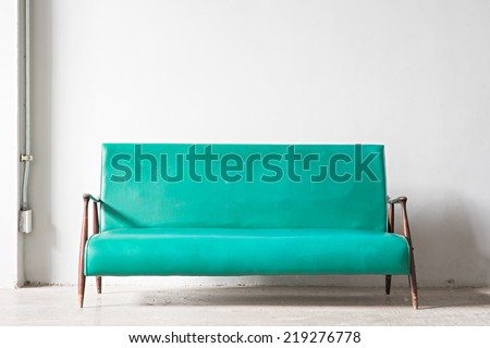 Green vintage sofa with white wall - stock photo