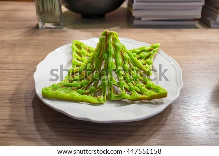 Green waffle steamed custard pile on white dish in bakery cafe - stock photo