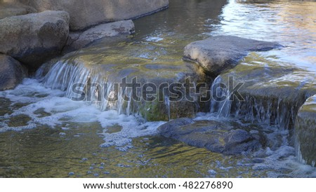 Green water flowing from decorative boulders and rocks, Cortez lake, small recreational park in North West Phoenix, AZ