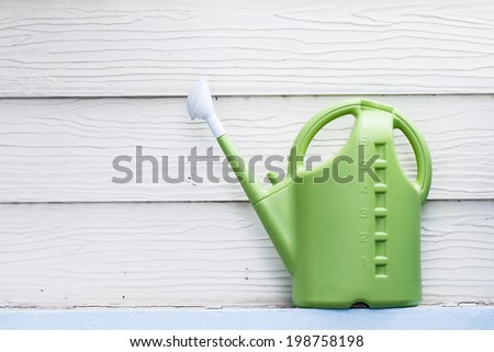 Green watering can on wooden background - stock photo