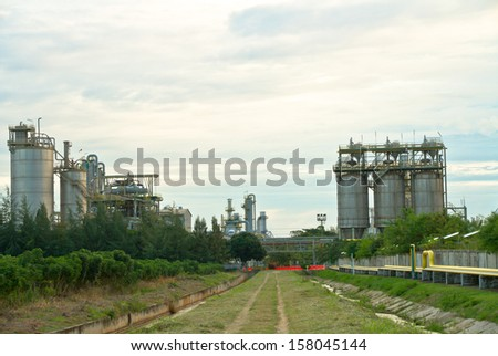 Green way and building in chemical plant under cloudy sky - stock photo