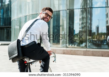 Green way to get to office. Rear view of joyful young businessman looking at camera and smiling while riding on his bicycle with office building in the background - stock photo