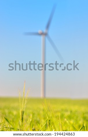 Green wheat field with blue sky and wind power Energy Generator in the background