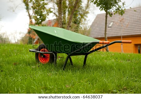 Green wheel barrow on the grass in the garden