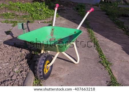 Green wheelbarrow parked  - stock photo
