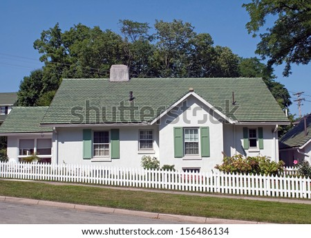 Green & White Cottage with Picket Fence - stock photo