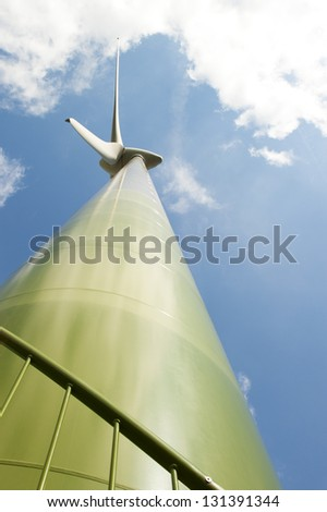 Green wind turbine taken upwards from a close-up position and silhouetted against a blue and partially cloudy sky - stock photo