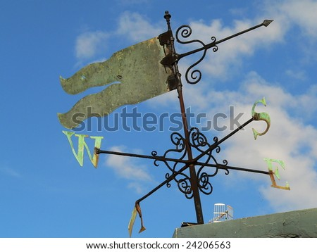 green wind vane in a blue, almost cloudless sky