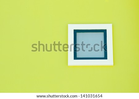 green window against a green wall - stock photo