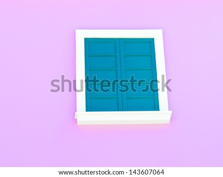 green window against a pink wall - stock photo