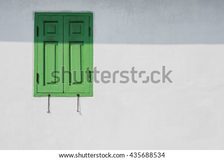 Green window on a white wall with shade . You can fill idea or text into space.