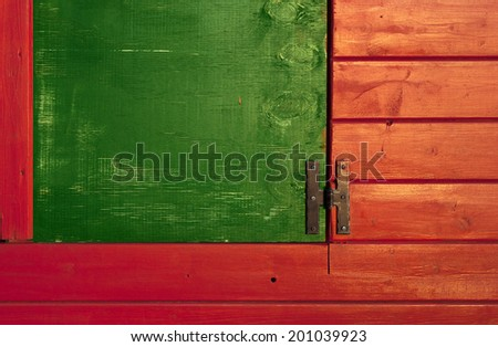 green window on red planks