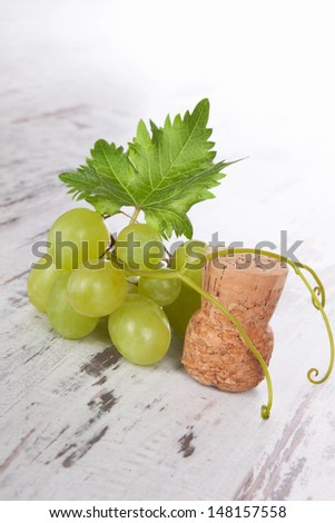 Green wine grapes with champagne cork on white wooden textured background. Vintage luxurious wine drinking. - stock photo