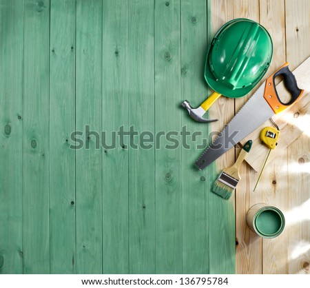 green wood floor with a brush, paint, tools and helmet - stock photo