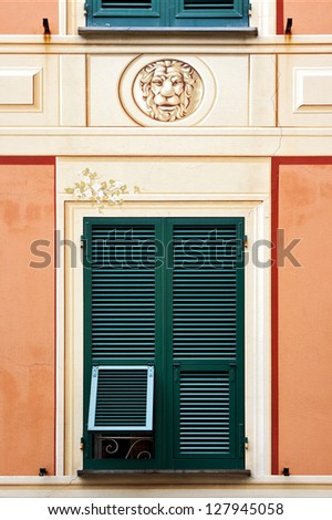 green wood venetian blind a  pink yellow red  wall and a head of lion  in the centre chiavari italy