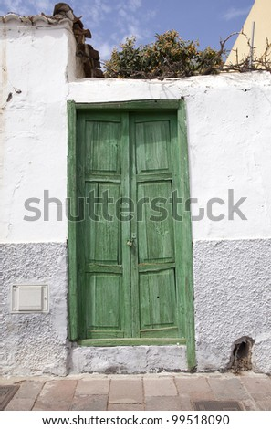 Green wooden door in a white wall in Spain - stock photo