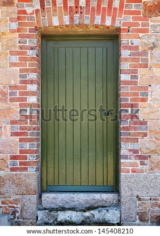 green wooden door set in red brick wall - stock photo
