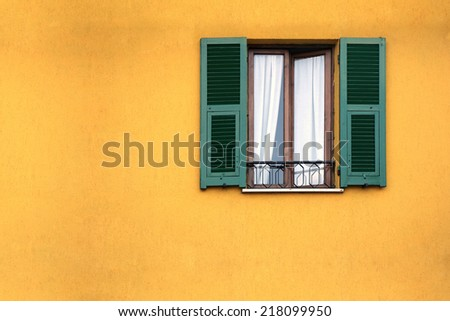 Green wooden window on the yellow facade  - stock photo