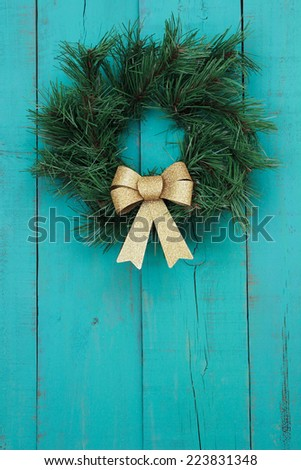 Green wreath with gold bow on antique teal blue rustic wood door - stock photo
