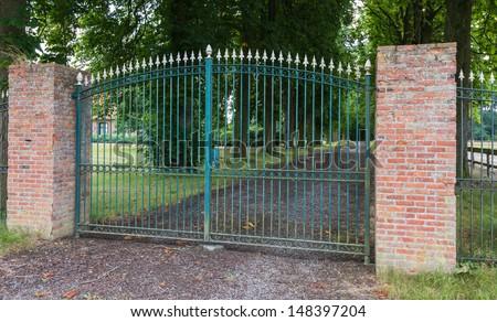 Green wrought iron gate between two masonry brick pillars - stock photo