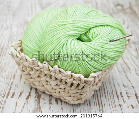 Green yarns and crotchet hook on a wooden background - stock photo