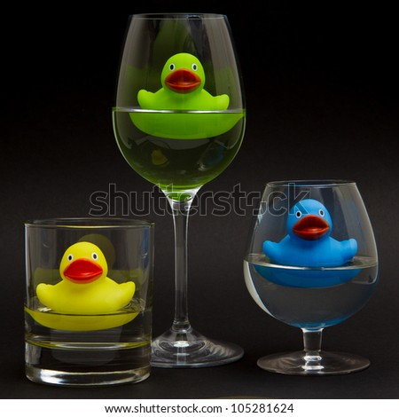 Green, yellow and blue rubber duck in different glasses on a dark background - stock photo
