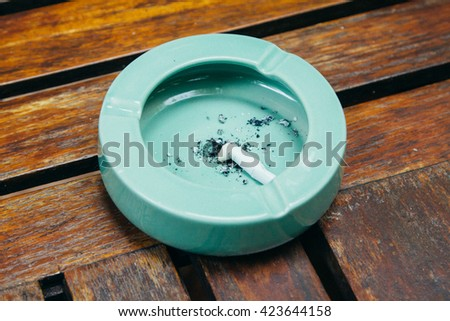 greenceramic ashtray full of smokes cigarettes - stock photo