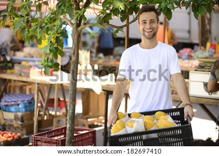Greengrocer owner of a small business at an open street market, selling organic fruits and vegetables, carrying a box full of papaya. - stock photo