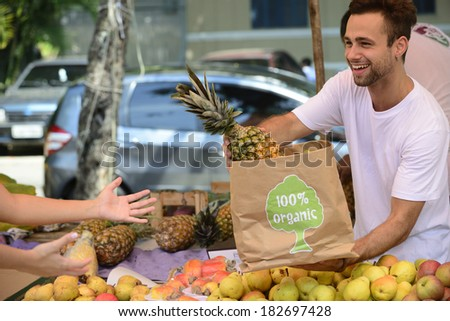 Greengrocer owner of a small business at an open street market, selling organic fruits and vegetables. - stock photo